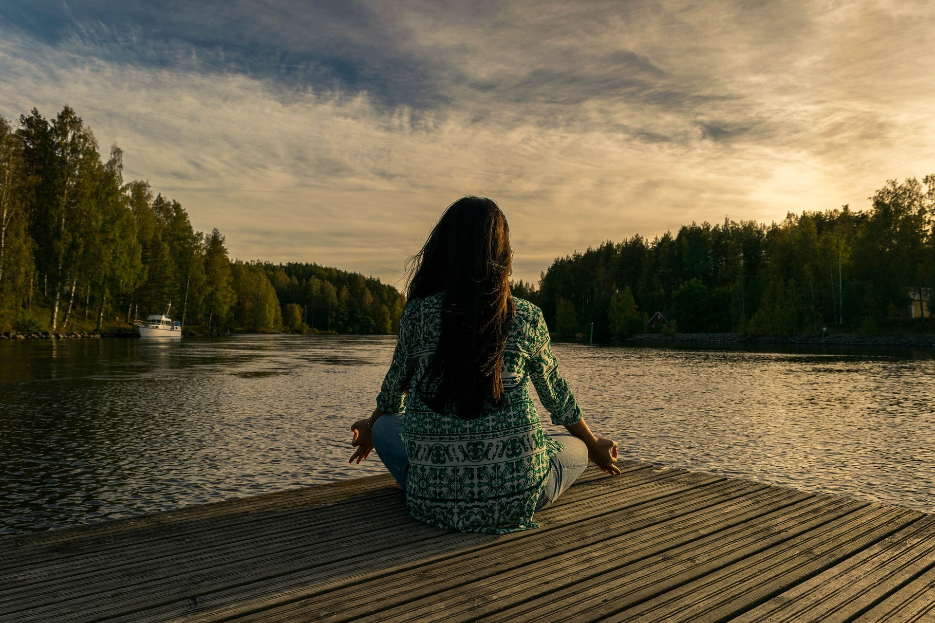 Long hair woman meditate on wooden deck on a lake