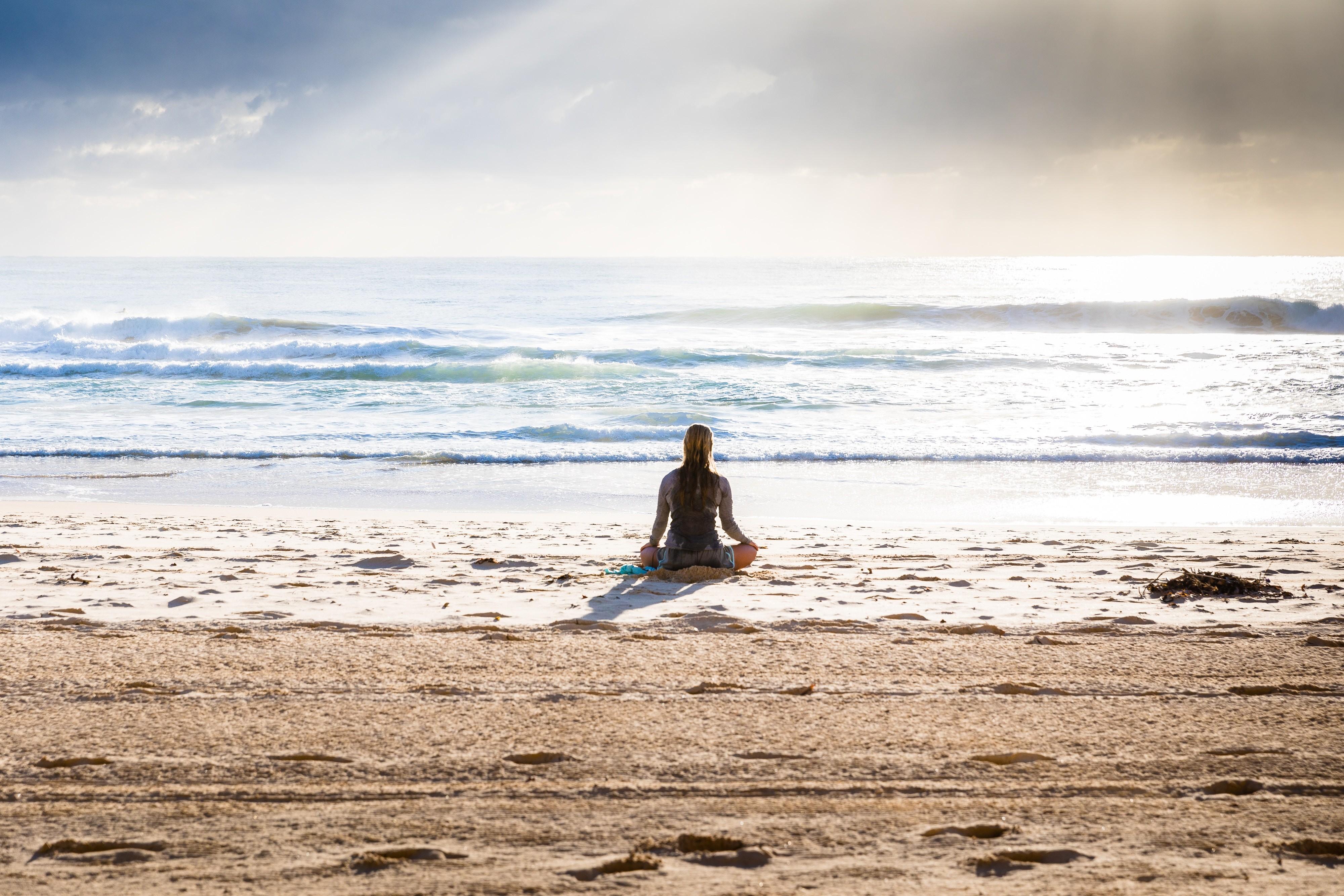 woman meditates at the beach